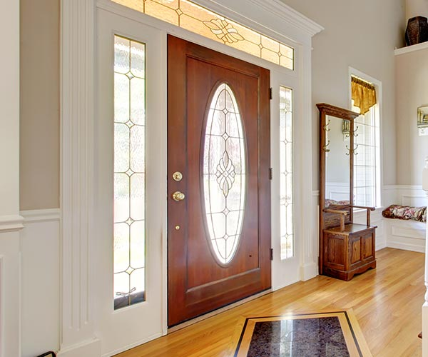 Front Door - A room that has a clock at the top of a wooden door - Staircases